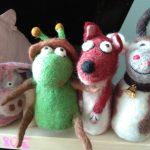 eine gefilzte grüne Schnecke, ein gefilzter Fuchs und eine Gefilzte Kuh sitzen als Fingerpuppen auf einem Regal