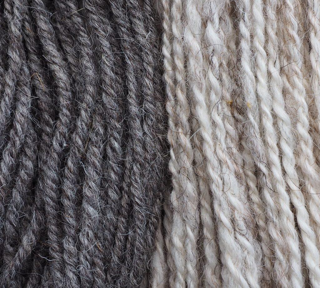 Nahaufnahme eines grauen und eines hellen Garns mit unterschiedlichen Zwirnwinkeln.